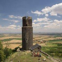 Jedna z věží hradu Házmburk, v pozadí je Říp.