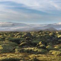 Rozsáhlé lávové pole a nad ním ledovec Vatnajökull