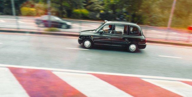Panning - ostré auto, pohybově máznuté pozadí. Foceno na čas 1/50 sekundy. Londýn, taxi
