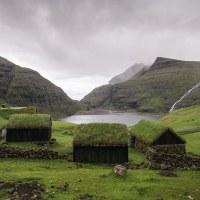 Saksun - malá vesnička obkopená kopci a vodopády. Jezero za domky je součást oceánu.